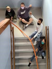 Science students sitting in stairwell while working on a hot wheel simulation